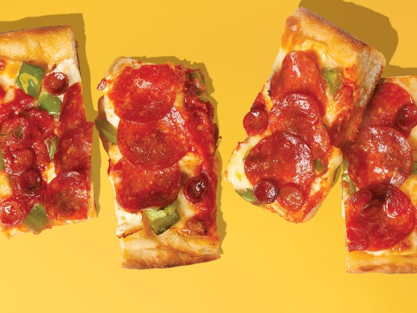 4 rectangle slices of Detroit-style pepperoni pizza on a yellow background.