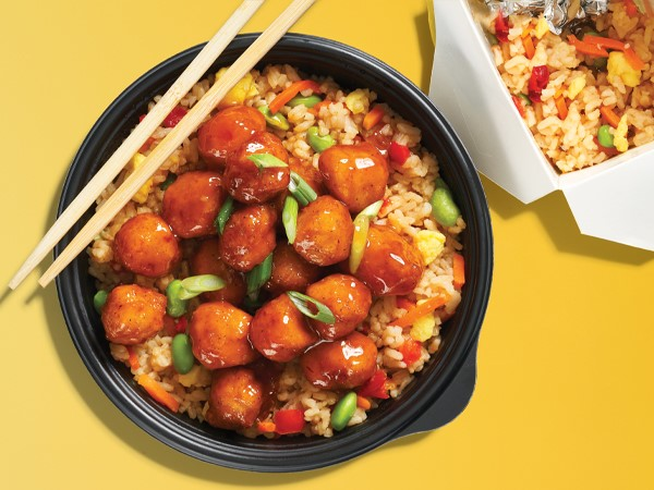 A black plastic bowl filled with orange chicken and fried rice, topped with chopsticks, and next to a white take out box on a yellow background.
