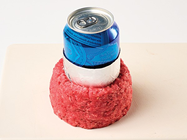 Ground beef formed around a foil-wrapped blue beer can on a white background.