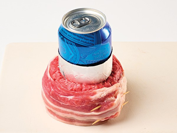 Bacon-wrapped ground beef formed around a foil-wrapped blue beer can on a white background.