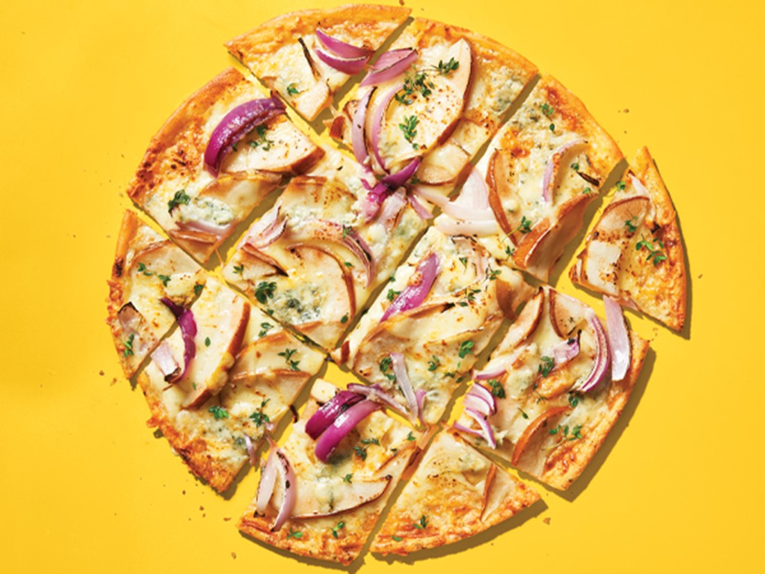 Gluten-free pizza with blue cheese, pear, and onions on a yellow background