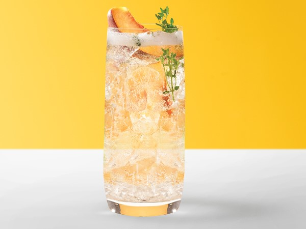 Ginger-peach spritzer in an ice-filled cocktail glass on a white and yellow background.