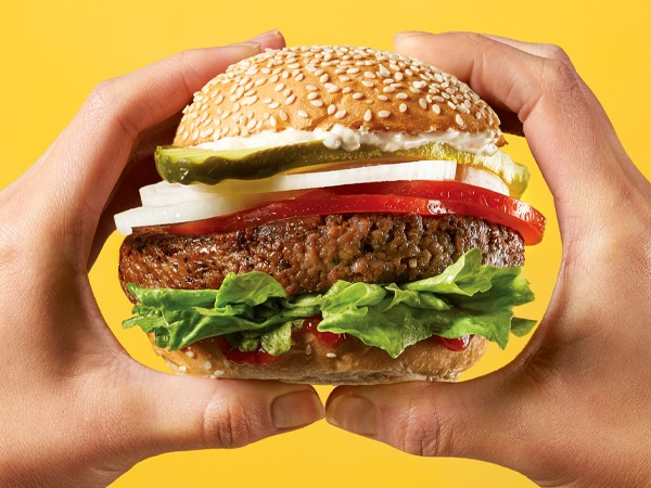 A plant-based burger topped with lettuce, ketchup, tomato slices, onion slices, pickle slices, and mayonnaise on a sesame seed bun, held with two hands on a yellow background.
