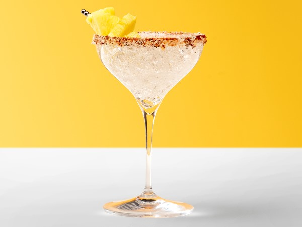 Spritzer margarita in a martini glass garnished with pineapple chunks on a white and yellow background.
