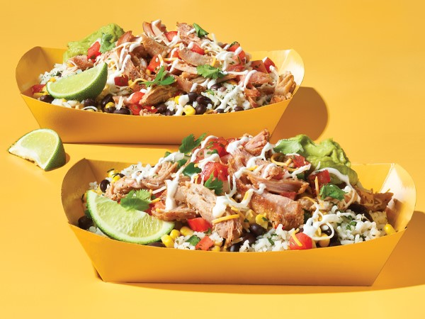 Pulled pork burrito bowls in rectangle yellow takeout boats on a yellow background.