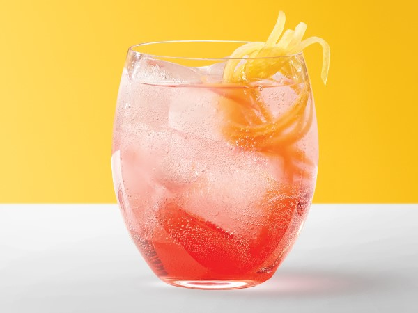 Red spritzer in an ice-filled glass garnished with lemon peels on a white and yellow background.