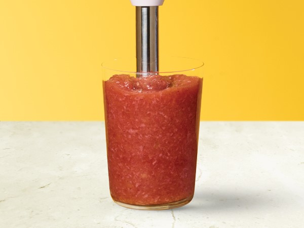 Strawberry applesauce in a glass with an immersion blender in the applesauce on a white and yellow background.