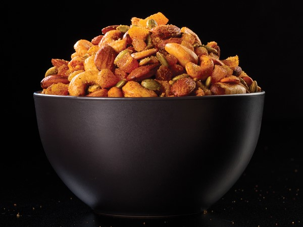 A bowl of mixed nuts in a black bowl on a black background.