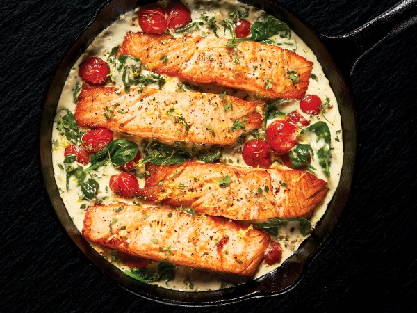 Four salmon fillets in a cast-iron skillet of creamy sauce, tomatoes, and spinach on a black background.