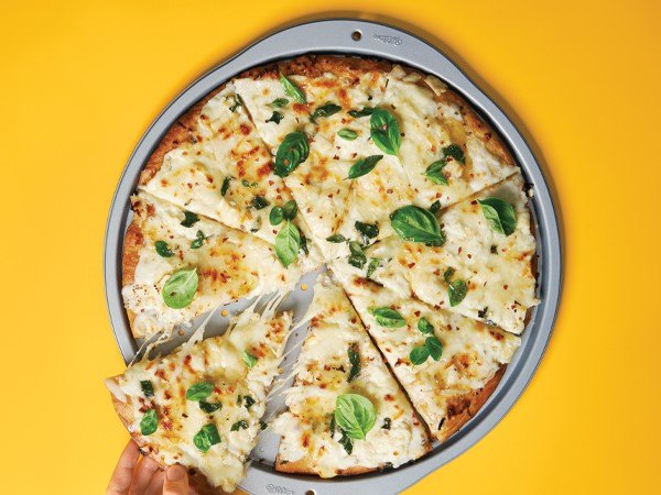 Alfredo pizza garnished with spinach on a metal pizza pan with a yellow background