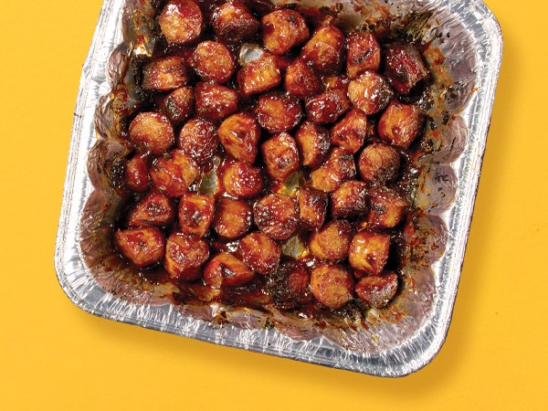 Brat burnt ends in a tin-foil square container on a yellow background.