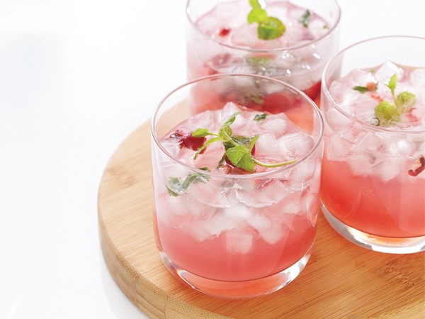 Three glasses of cherry mojitos centered on a wooden serving plate on a white background.