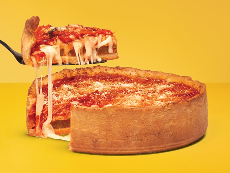 Chicago-style pizza with one slice raised on a black spatula above the pizza on a yellow background.
