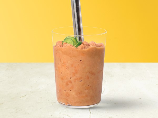 Light-orange colored chili-refried beans in a glass with an immersion blender inserted on a white and yellow background.