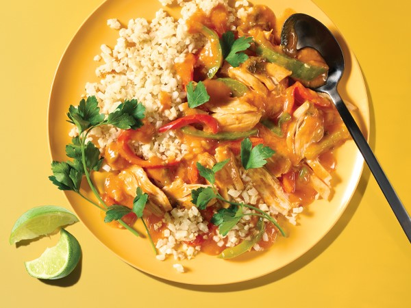 Coconut chicken curry on a yellow plate with a spoon and lime wedges on a yellow background.