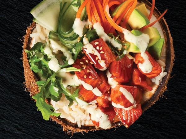 Salmon, cucumber and carrot ribbons, arugula, avocado chunks, and rice in a coconut bowl on a black background.