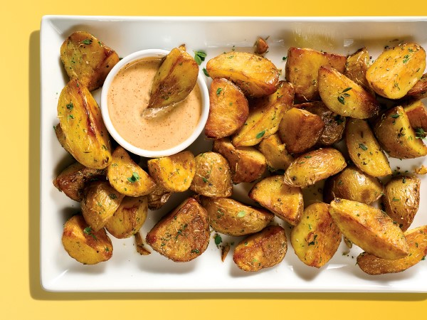 A white serving plate with roasted potato wedges next to a ramekin of dipping sauce on a yellow background.