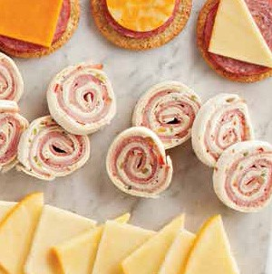 Cream cheese and ham pinwheels next to sliced cheese, meat and crackers
