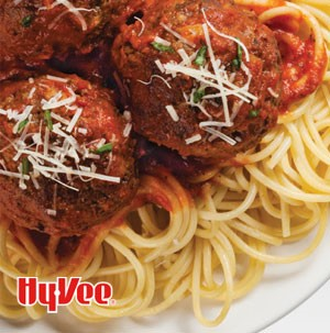Spaghetti topped with red sauce, meatballs, shredded cheese and chopped parsley