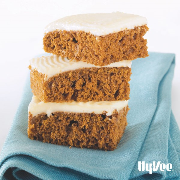 Cut and stacked pumpkin bars with cream cheese frosting on a blue napkin