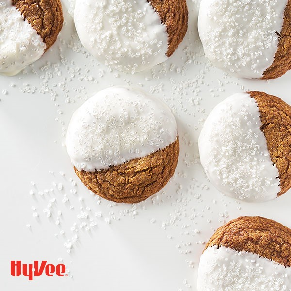 Molasses cookies half dipped in white chocolate and topped with white coarse sugar