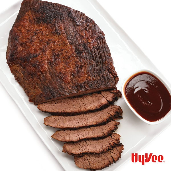 Platter of a partially-sliced beef brisket with a side dish of barbecue sauce