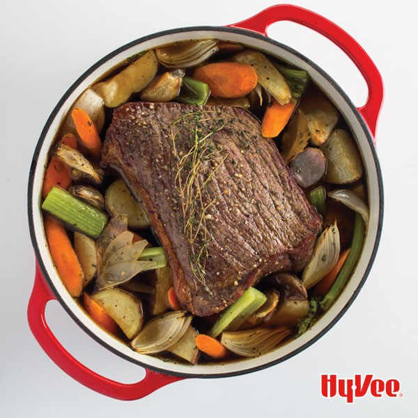 Red Dutch oven filled with large slices of carrots, potatoes, celery, onions with pork roast garnished with thyme sprigs in center