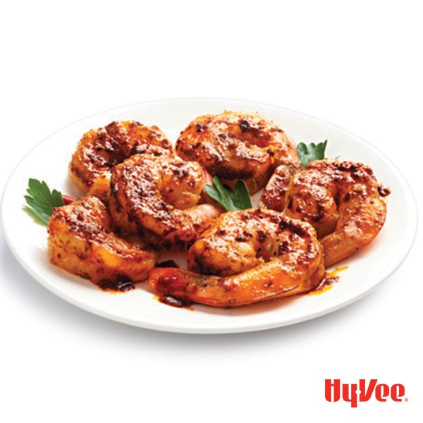 Shrimp on a plate with parsley and drizzled with sauce