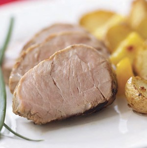 Sliced grilled pork loin with a side of roasted potatoes