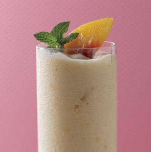 Yellow smoothie in a clear glass garnished with fresh peach slice and fresh mint leaves