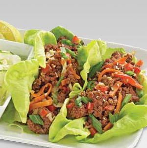 Lettuce wraps filled with ground meet and topped with shredded carrots, chopped bell peppers, and sliced green onions
