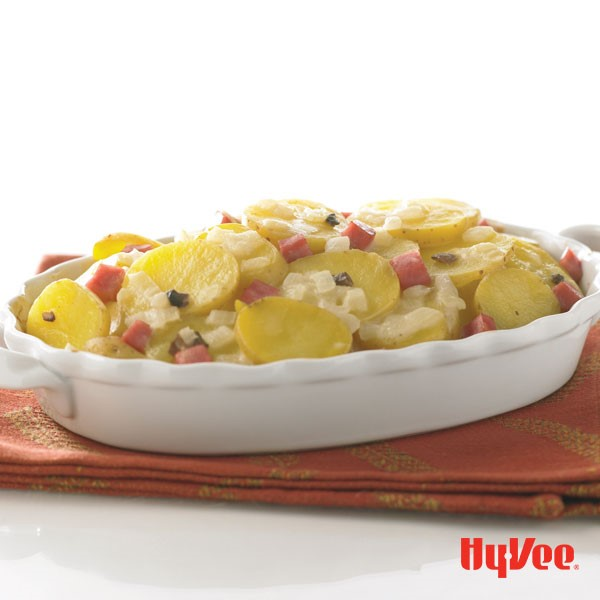Sliced potatoes topped with chopped ham and onions