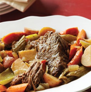 Bowl of pot roast surrounded by roasted vegetables