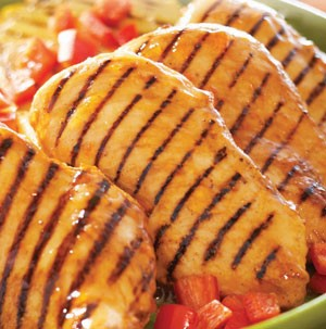 Grilled and glazed chicken breasts on green plate