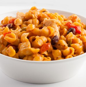 Bowl of shell pasta, black beans, and corn mixed in cheese sauce