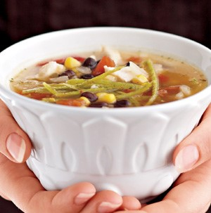 Hands holding white bowl of soup filled with chicken, black beans, corn, and thinly sliced tortilla strips