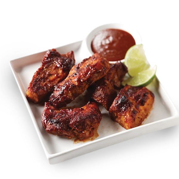 Country-style ribs on a plate with barbecue sauce and lime wedges