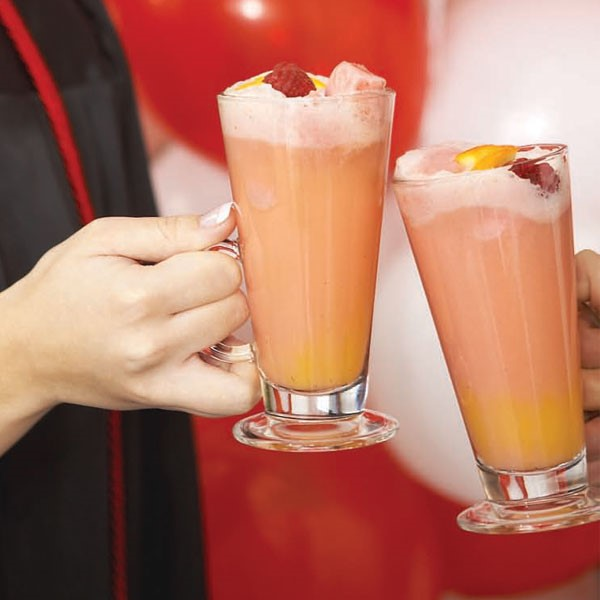 Glasses filled with orange and red raspberry orange punch with foam  at the top and topped with orange wedge and whole raspberry