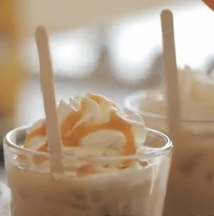 Iced coffee topped with whipped cream and drizzled with caramel sauce with a wooden coffee stir stick