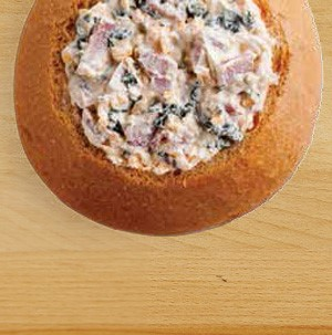 Bread bowl filled with baked ham and cheese dip