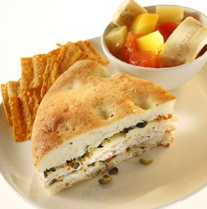 Muffaletta sandwich with olives, chicken, and focaccia bread with a side of mixed fruit and chips