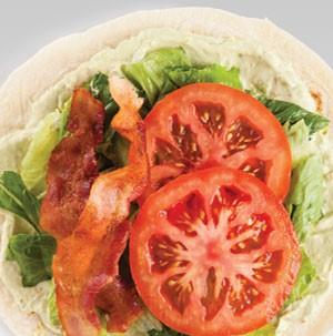 Tortilla wrap filled with avocado spread, bacon, lettuce and tomato
