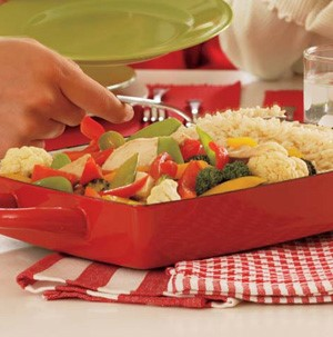 Red casserole pan filled with mixed vegetables, rice, and chicken