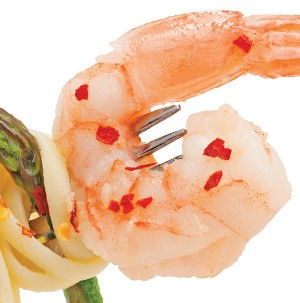 Cooked shrimp  with tail on a fork garnished with red pepper flakes