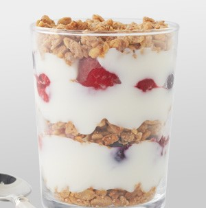 Glass filled with layers of granola, fresh fruit, and yogurt