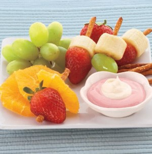 Mixed fruit kabobs made from pretzel sticks with fruit dip on the side