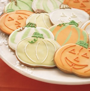 Plate of pumpkin-decorated cookies in green, white and orange icing