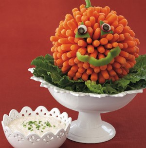 White cake stand topped with lettuce and carrots to look like a pumpkin and white dip on the side
