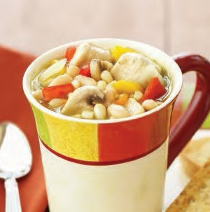 Mug filled with chicken chili with diced mixed vegetables