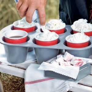 Popover pan filled with red solo cups holding hot cocoa and whipped cream topping
